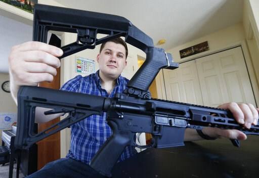 (AP Photo/Steve Helber). In this March 15, 2019 photo, Ryan Liskey displays a bump stock on top of his AR-15 at his home in Harrisonburg, Va. The ban on bump stocks is just a few days away and owners of the devices like Liskey are trying to figure out ...