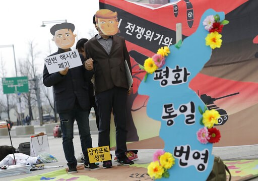 (AP Photo/Lee Jin-man). Protesters wearing masks of U.S. President Donald Trump and North Korean leader Kim Jong Un stand near the map of Korean Peninsula during a rally demanding the denuclearization of the Korean Peninsula and peace treaty near the U...
