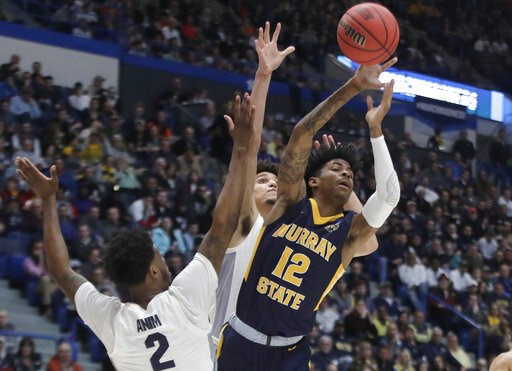 (AP Photo/Elise Amendola). Murray State's Ja Morant (12) passes the ball under pressure from Marquette's Sacar Anim (2) and Brendan Bailey, behind, during the first half of a first round men's college basketball game in the NCAA Tournament, Thursday, M...
