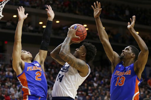 (AP Photo/Nati Harnik). Nevada's Jordan Caroline (24) shoots between Florida's Andrew Nembhard (2) and Kevarrius Hayes (13) during the first half of a first round men's college basketball game in the NCAA Tournament in Des Moines, Iowa, Thursday, March...