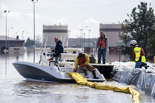 (Delanie Stafford, The U.S. Air Force via AP). In this March 18, 2019 photo released by the U.S. Air Force, environmental restoration employees deploy a containment boom from a boat on Offutt Air Force Base in Neb., as a precautionary measure for possi...