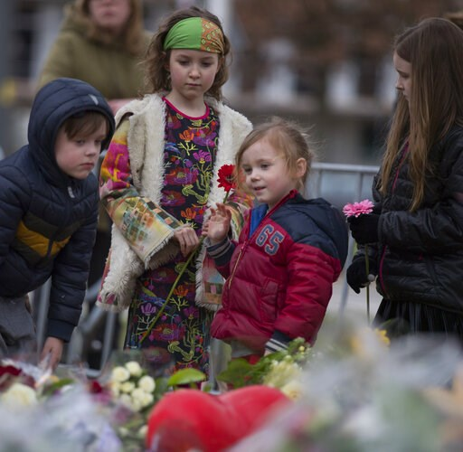 (AP Photo/Peter Dejong). Children lay flowers at a makeshift memorial site for the victims of a shooting incident in a tram in Utrecht, Netherlands, Tuesday, March 19, 2019. A gunman killed three people and wounded others on a tram in the central Dutch...