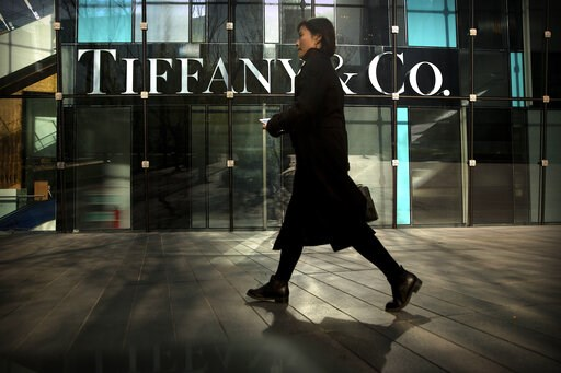(AP Photo/Mark Schiefelbein, File). FILE- In this Nov. 29, 2018, file photo, a woman walks past a Tiffany & Co. store at a shopping mall in Beijing. Tiffany & Co. reports financial results on Friday, March 22, 2019.