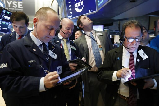 (AP Photo/Richard Drew, File). FILE- In this March 13, 2019, file photo traders gather at the post that handles Oaktree Capital Group on the floor of the New York Stock Exchange. The U.S. stock market opens at 9:30 a.m. EDT on Friday, March 22.