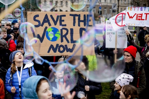 "(Christoph Soeder/dpa via AP). Young people protest for climate action with a sign reading 'Save the World Now"" during a  'Friday for Future' demonstration in Berlin, Germany, Friday, March 22, 2019."