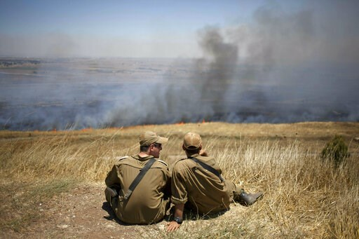 (AP Photo/Ariel Schalit, File). FILE - In this July 16, 2013, file photo, Israeli soldiers sit in a position on the border with Syria on the Israeli-controlled Golan Heights as smoke rises following explosions of mortar shells. President Donald Trump's...