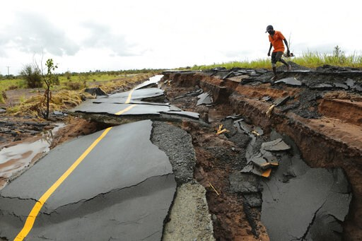 (AP Photo/Tsvangirayi Mukwazhi). A man passes through a section of the road damaged by Cyclone Idai in Nhamatanda about 50 kilometres from Beira, in Mozambique, Friday March, 22, 2019. As flood waters began to recede in parts of Mozambique on Friday, f...