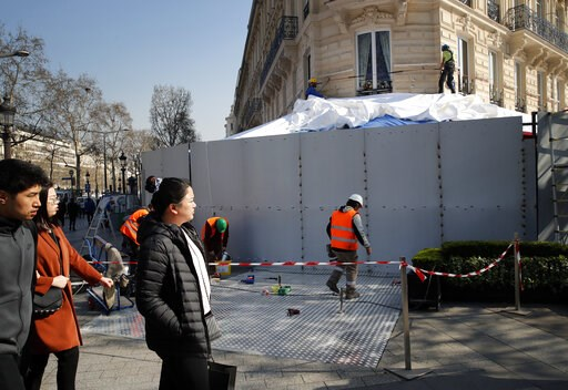 (AP Photo/Christophe Ena). Tourists watch workers as they set up steel protections on the famed restaurant Fouquet's in Paris, Friday, March 22, 2019. French President Emmanuel Macron has announced that soldiers will be deployed across the country to h...