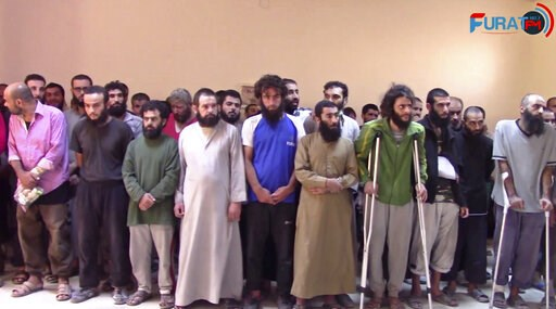(Furat FM, via AP, File). FILE - In this frame grab from a video released In this Oct. 15, 2017, file photo and provided by Furat FM, a Syrian Kurdish activist-run media group, shows Syrian Islamic State group fighters who have surrendered, at a base o...