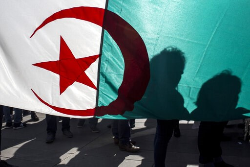 (AP Photo/Rafael Yaghobzadeh). Demonstrators are silhouetted against a national Algerian flag as they stage a protest on the Republique Plaza to press for an end to the 20-year-rule of Algerian President Abdelaziz Bouteflika, in Paris, France, Sunday, ...