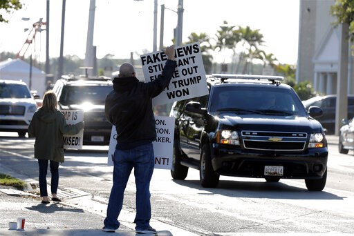 (AP Photo/Terry Renna). People hold signs as the motorcade of President Donald Trump passes on Saturday, March 23, 2019, in West Palm Beach, Fla. Special counsel Robert Mueller closed his long and contentious Russia investigation with no new charges, e...