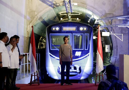 "(AP Photo/Dita Alangkara, Pool). Indonesian President Joko ""Jokowi"" Widodo, center, stands on a stage with the background of a Jakarta Mass Rapid Transit train during the inauguration ceremony of the subway line in Jakarta, Indonesia, Sunday, March 24,..."