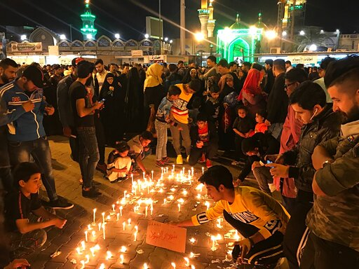 (AP Photo/Farid Abdulwahed). Shiite Muslim worshippers light candles as they pray for the victims of a sunken ferry, outside the golden-domed Shiite shrine of Imam Moussa al-Kadhim, in Baghdad, Iraq, Friday, March 22, 2019. A ferry overloaded with peop...
