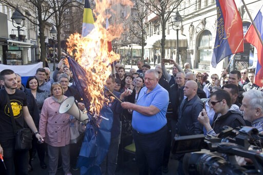 (AP Photo/Marko Drobnjakovic). Vojislav Seselj, center, the leader of the ultranationalist Serbian Radical Party, holds a burning NATO flag as he and others gather for a protest in Belgrade, Serbia, Sunday, March 24, 2019. Members of the ultranationali...