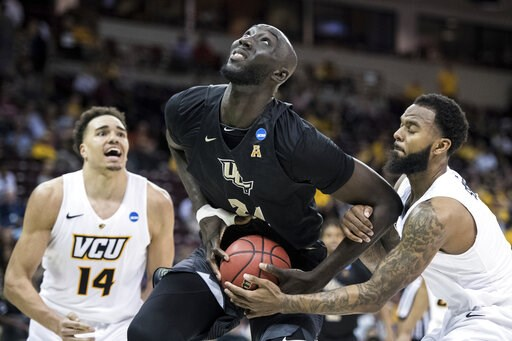 (AP Photo/Sean Rayford). Central Florida center Tacko Fall (24) is fouled by VCU guard Mike'L Simms, right, during the second half of a first-round game in the NCAA men's college basketball tournament Friday, March 22, 2019, in Columbia, S.C. Central F...