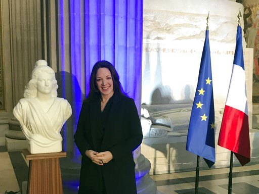 (AP Photo/Thomas Admason). Britain's Catherine Norris Trent poses next to a bust of Marianne, left, symbol of the French Republic, and the French, right, and European flags after a naturalization ceremony in Paris' Pantheon monument, Thursday, March 21...