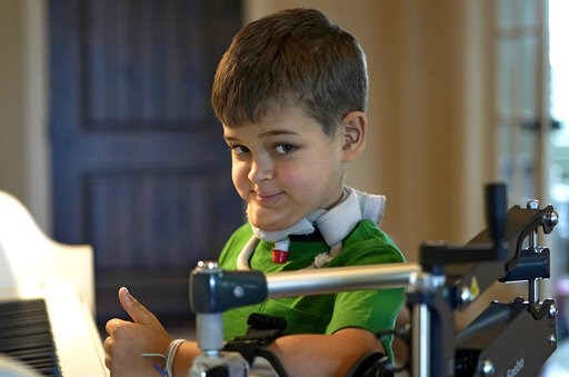 (AP Photo/David J. Phillip). Braden Scott gives a thumbs up as he pauses while practicing on the piano in Tomball, Texas on Friday, March 29, 2019. Braden was diagnosed with the mysterious syndrome called acute flaccid myelitis, or AFM, in 2016 and was...