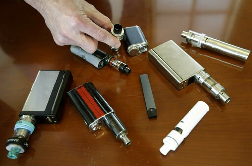 (AP Photo/Steven Senne, File). FILE - In this April 10, 2018, file photo, a high school principal displays vaping devices that were confiscated from students in such places as restrooms or hallways at the school in Massachusetts. On Wednesday, April 3,...