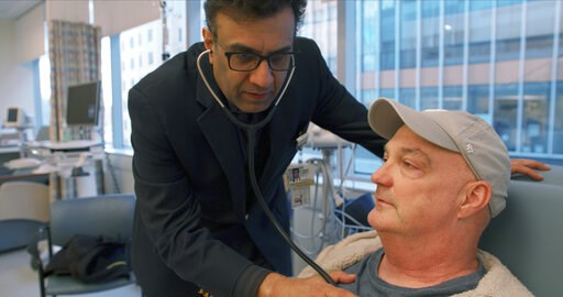 (Adam Knee/Brigham and Women's Hospital via AP). In this February 2019 photo provided by Brigham and Women's Hospital, Dr. Mandeep Mehra, executive director of Brigham's Center for Advanced Heart Disease, checks on patient James Sullivon at the hospita...