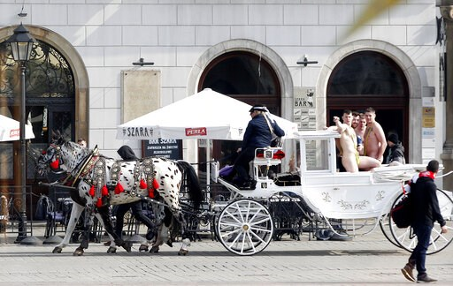 (AP Photo/Czarek Sokolowski). In this photo taken on Friday March 29, 2019, tourists wearing mankinis travel in a horse cab in Market Square in Krakow, Poland. Police in southern Poland say they are investigating four English-speaking tourists spotted ...