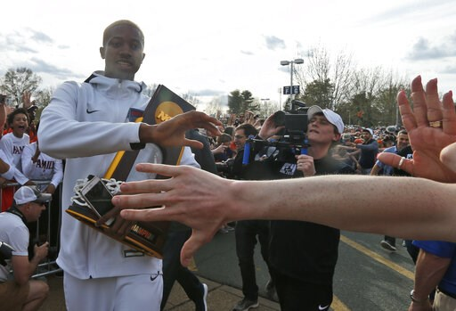 (AP Photo/Steve Helber). Mamadi Diakite hoods the NCAA championship trophy as Virginia team members are welcomed by fans as they return to Charlottesville, Va., Tuesday, April 9, 2019, the day after defeating Texas Tech in the title game of college bas...