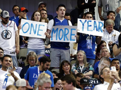"""(AP Photo/Tony Gutierrez). Dallas Mavericks' Dirk Nowitzki fans hold up signs reading, """"One more year,"""" during the first half of the team's NBA basketball game against the Phoenix Suns in Dallas, Tuesday, April 9, 2019. The team was playing its final h..."""