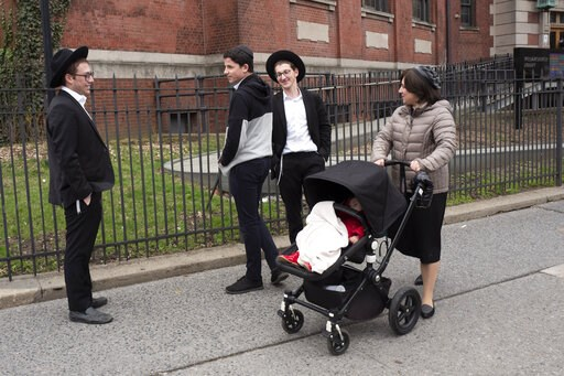 (AP Photo/Mark Lennihan). A woman, right, who identified herself as Ester, passes a group of boys, Tuesday, April 9, 2019, in the Williamsburg section of Brooklyn, New York. Ester says that she does not believe that the measles vaccination is safe. The...