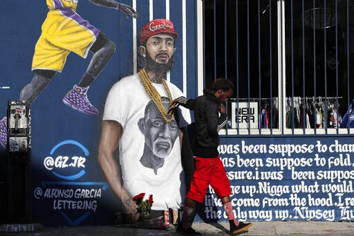 (AP Photo/Jae C. Hong). A man touches a mural depicting slain rapper Nipsey Hussle, Tuesday, April 2, 2019, in Los Angeles. Hussle was shot and killed Sunday, March 31, outside of his clothing store in Los Angeles.