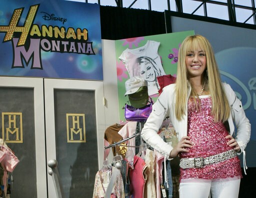 "(AP Photo/Mary Altaffer, File). FILE - In this June 19, 2007 file photo Miley Cyrus, star of The Disney Channel's series ""Hannah Montana"" makes an appearance at the Licensing International Expo in New York. Costumes, props and tour items from the Disne..."