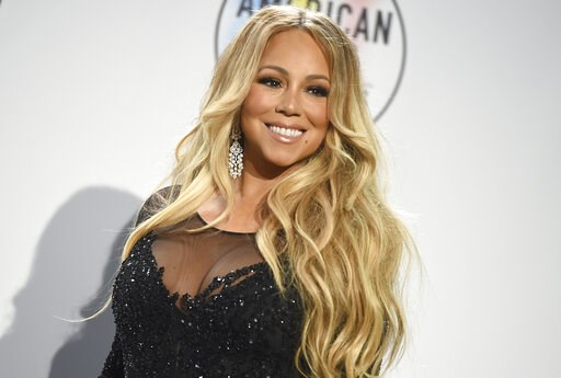 (Photo by Jordan Strauss/Invision/AP, File). FILE - In this Oct. 9, 2018, file photo Mariah Carey poses in the press room at the American Music Awards at the Microsoft Theater in Los Angeles. No artist has more No. 1 hits on the Billboard Hot 100 chart...