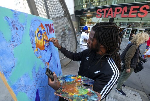 (AP Photo/Ringo H.W. Chiu). Artist Gift Davis works on a portrait of rapper Nipsey Hussle as fans wait in line to attend a public memorial at Staples Center in Los Angeles, Thursday, April 11, 2019. Hussle was killed in a shooting outside his Marathon ...