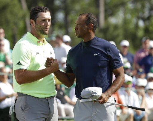 (AP Photo/Marcio Jose Sanchez). Tiger Woods shakes hands with Jon Rahm, of Spain, after their first round for the Masters golf tournament Thursday, April 11, 2019, in Augusta, Ga.