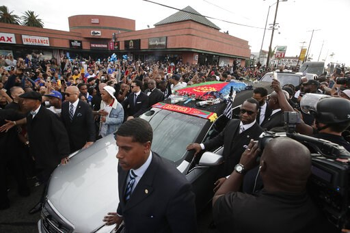 (AP Photo/Jae C. Hong). People watch as a hearse carrying the casket of slain rapper Nipsey Hussle passes Hussle's clothing store The Marathon, Thursday, April 11, 2019, in Los Angeles. Hussle's casket, draped in the flag of his father's native country...