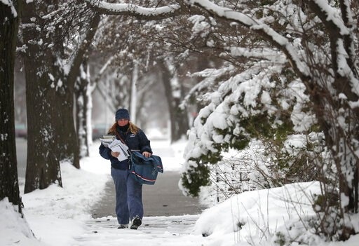 (Dan Powers/The Post-Crescent via AP). Ginny Klein, a city letter carrier assistant, delivers mail in windy sleeting conditions during a spring snow storm Thursday, April 11, 2019, in Oshkosh, Wis. The second major snowstorm in the region in a month le...