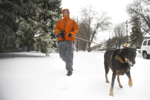 (Briana Sanchez/The Argus Leader via AP). David Heinold walks his dog Max through the snow Thursday, April 11, 2019, in Sioux Falls, S.D. Heavy snow and strong winds hammered parts of the central U.S. on Thursday, knocking out power to tens of thousand...