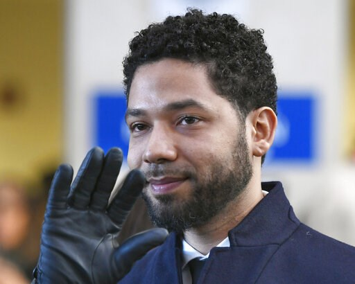 "(AP Photo/Paul Beaty, File). FILE - In this March 26, 2019, file photo, actor Jussie Smollett smiles and waves to supporters before leaving Cook County Court after his charges were dropped in Chicago. The city of Chicago is suing ""Empire"" actor to reco..."