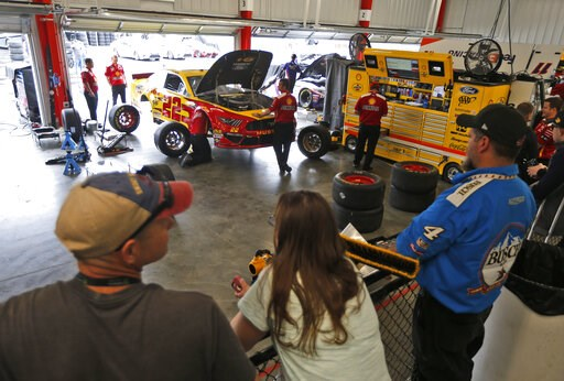 (AP Photo/Steve Helber). Fans watch the team of Joey Logano as they work on the car in the garage at Richmond International Raceway in Richmond, Va., Friday, April 12, 2019.