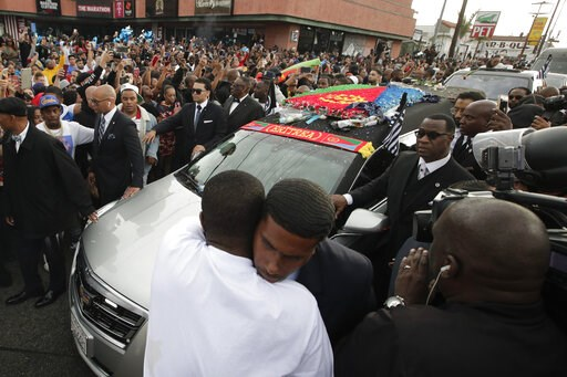 (AP Photo/Jae C. Hong). Two men hug as a hearse carrying the casket of slain rapper Nipsey Hussle passes through the crowd Thursday, April 11, 2019, in Los Angeles. The 25-mile procession traveled through the streets of South Los Angeles after his memo...