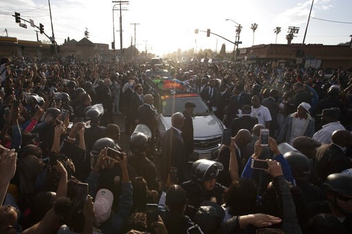(AP Photo/Jae C. Hong). A hearse carrying the casket of slain rapper Nipsey Hussle passes through a large crowd on its 25-mile trek through the streets of the city Thursday, April 11, 2019, in Los Angeles. Hussle was shot and killed March 31 outside hi...