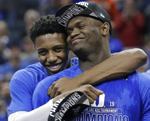 (AP Photo/Nell Redmond, File). FILE - In this March 16, 2019, file photo, Duke's RJ Barrett, left, hugs Zion Williamson after Duke defeated Florida State in the NCAA college basketball championship game of the Atlantic Coast Conference tournament, in C...