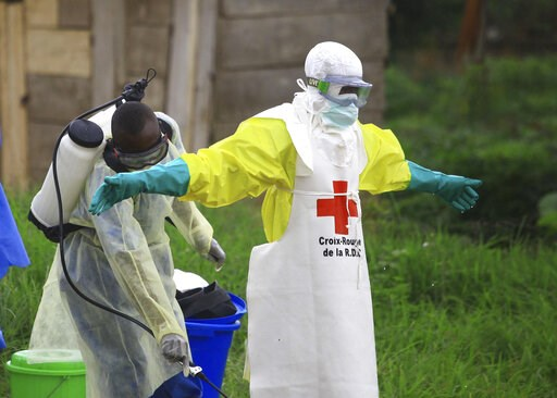 (AP Photo/Al-hadji Kudra Maliro, File). FILE - In this Sunday, Sept 9, 2018 file photo, a health worker sprays disinfectant on his colleague after working at an Ebola treatment center in Beni, eastern Congo.  Top Red Cross official Emanuele Capobianco ...