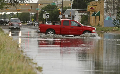 (Jacob Ford/Odessa American via AP). A vehicle drives through a flooded section of Muskingum Avenue on Saturday, April,13, 2019, in Odessa, Texas.