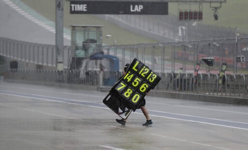 (AP Photo/Eric Gay). A crew member moves signage during a weather delay for practices and qualifying for the Grand Prix of the Americas motorcycle race at the Circuit Of The Americas, Saturday, April 13, 2019, in Austin, Texas.