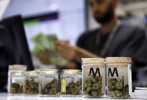 (AP Photo/John Locher, File). FILE - In this July 1, 2017, file photo, a cashier rings up a marijuana sale at the Essence cannabis dispensary in Las Vegas. Complaints that the state releases no information about who applies for and receives dispensary ...