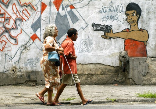 (AP Photo/Renzo Gostoli, File). FILE - In this Oct. 22, 2005 file photo, people walk past graffiti in Rio de Janeiro, Brazil, a day before a vote to ban the sale of firearms and ammunition to civilians. Backed by the Roman Catholic church and other pow...