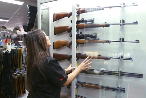 (AP Photo/Rick Rycroft). FILE - In this Wednesday, Oct. 4, 2017 file photo, a salesperson checks rifles in a gun shop display in Sydney, Australia. A documentary aired in March 2019 by Al Jazeera reported officials with Australia's far-right One Nation...
