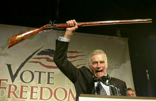 """(AP Photo/Jim Cole, File). FILE - In this Oct. 21, 2002 file photo, National Rifle Association President Charlton Heston holds up a rifle as he addresses gun owners during a """"get-out-the-vote"""" rally in Manchester, N.H. While American gun-rights are ens..."""