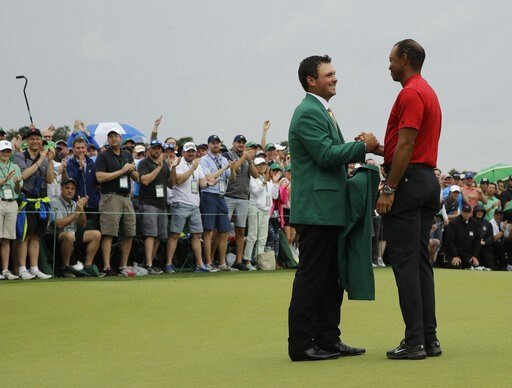 (AP Photo/Charlie Riedel). Patrick Reed helps Tiger Woods with his green jacket after Woods won the Masters golf tournament Sunday, April 14, 2019, in Augusta, Ga.