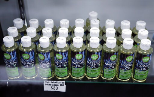 (AP Photo/Carlos Osorio, File). FILE - In this Nov. 7, 2018, file photo, bottles of massage oil with cannabidiol (CBD) and tetrahydrocannabinol (THC), two natural compounds found in plants of the Cannabis genus, are displayed at the Far West Holistic C...