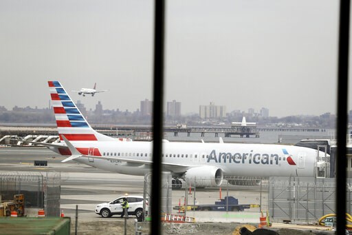 (AP Photo/Frank Franklin II, File). FILE - In a March 13, 2019 file photo, an American Airlines Boeing 737 MAX 8 sits at a boarding gate at LaGuardia Airport in New York. American Airlines is canceling 115 flights per day through mid-August because of ...